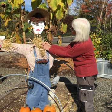 Jane Ostereicher perking up a scarecrow