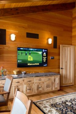 Home office's audio/video system with a low-profile, wall-mounted, touch-pad controller. A 10-inch subwoofer is concealed inside the cabinet. Every subwoofer in the home is hidden in this manner.