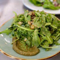 Wilted arugula salad; sautéed bacon, golden raisins & shallots over wild arugula tossed with a hazelnut vinaigrette, pumpkin seed pesto