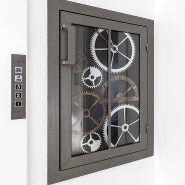 Dumb waiter, glass access doors mimic old elevator clockwork gears.