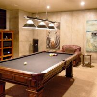 This inviting billiard room features a Samsung 75-inch 8K TV, AnthemAV audio/video processor, Aesthetix Atlas stereo amplifier, a pair of Focal Sopra No2 speakers and a JL Audio E112 subwoofer.