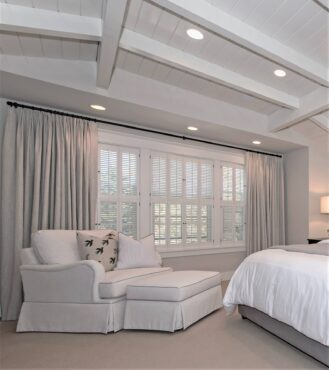 Pleated linen draperies paired with shutters