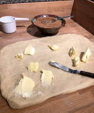 Spread soft butter onto dough.